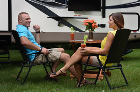 couple on camp chairs in front of 5th wheel RV